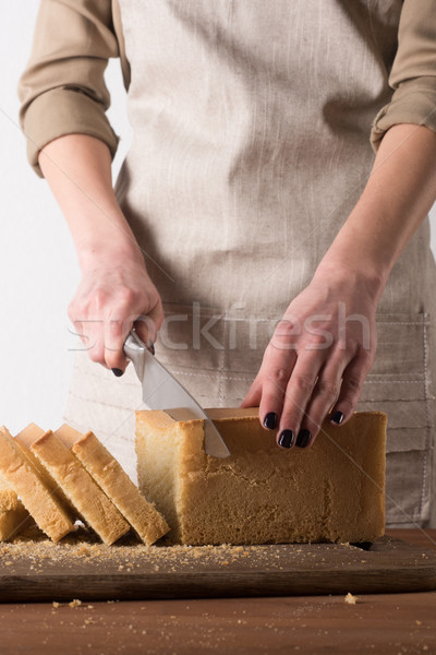 partial view of woman cutting bread into pieces on wooden cutting board Stock photo © LightFieldStudios