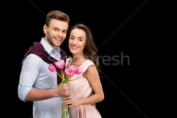 portrait of smiling couple in love holding tulips bouquet and looking to camera on black, internatio Stock photo © LightFieldStudios