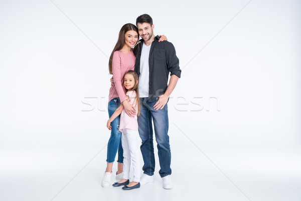 Happy young family with one child standing embracing on white Stock photo © LightFieldStudios