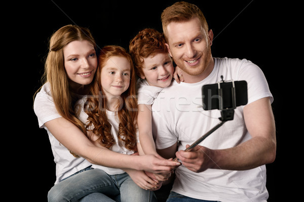 happy family taking selfie on smartphone isolated on black Stock photo © LightFieldStudios