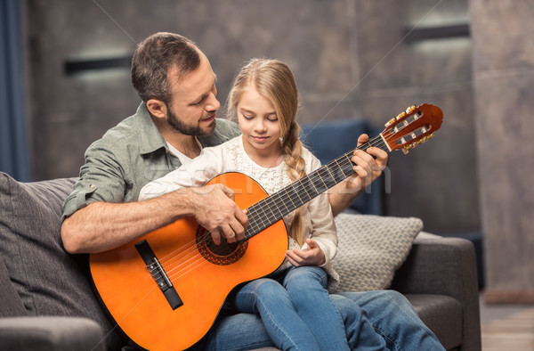 Father and daughter playing guitar Stock photo © LightFieldStudios
