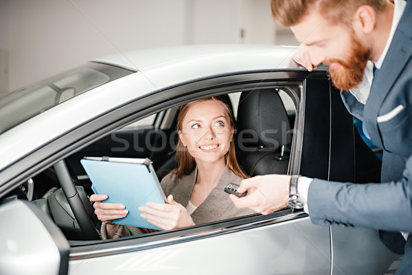 Bearded salesman giving car key to young woman sitting in new car with digital tablet Stock photo © LightFieldStudios
