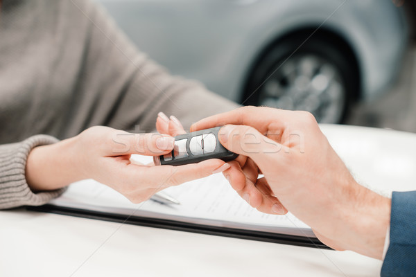 Close-up partial view of dealer giving car key to new owner Stock photo © LightFieldStudios
