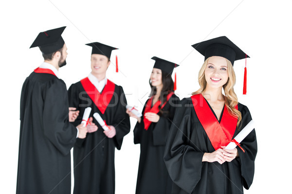 Happy young woman in mortarboard holding diploma and friends standing behind  Stock photo © LightFieldStudios