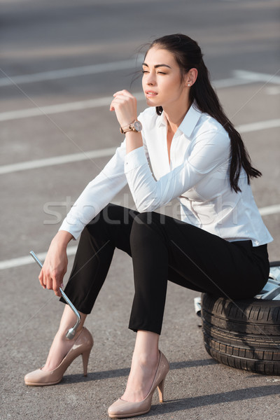 woman sitting on car tire Stock photo © LightFieldStudios