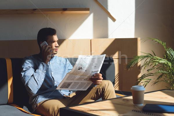 Férfi okostelefon olvas újság komoly fiatal Stock fotó © LightFieldStudios