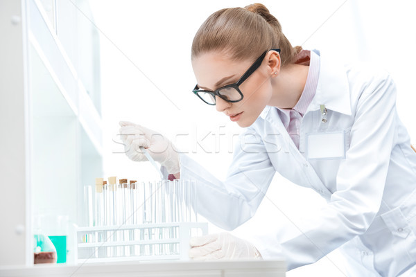 Young concentrated woman scientist in eyeglasses working with test tubes and pipette  Stock photo © LightFieldStudios