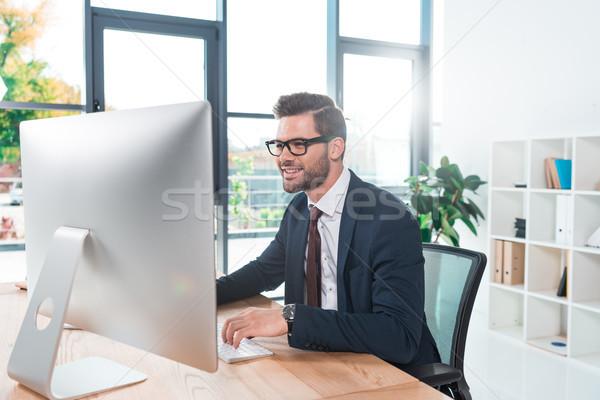 Stock fotó: üzletember · dolgozik · asztali · számítógép · mosolyog · fiatal · szemüveg