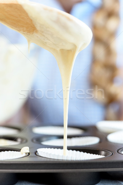 Close-up view of dough on wooden spoon and baking form for cupcakes Stock photo © LightFieldStudios