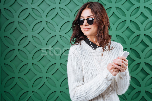 Woman in sweater and sunglasses listening to music  Stock photo © LightFieldStudios