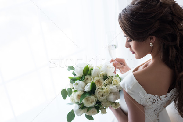 attractive bride in traditional dress with wedding bouquet and glass of champagne standing at window Stock photo © LightFieldStudios