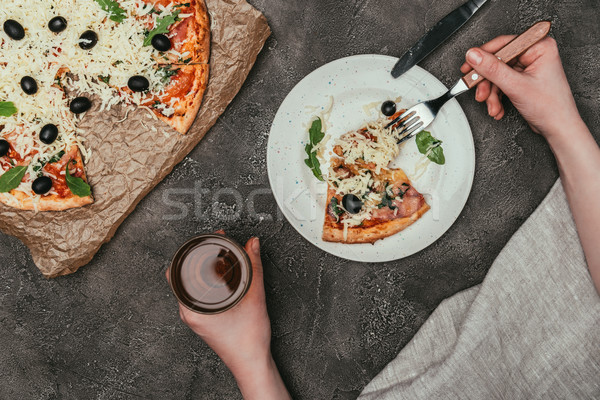 Close-up view of woman having dinner with pizza and drink on dark background Stock photo © LightFieldStudios