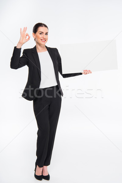 Businesswoman holding blank card Stock photo © LightFieldStudios