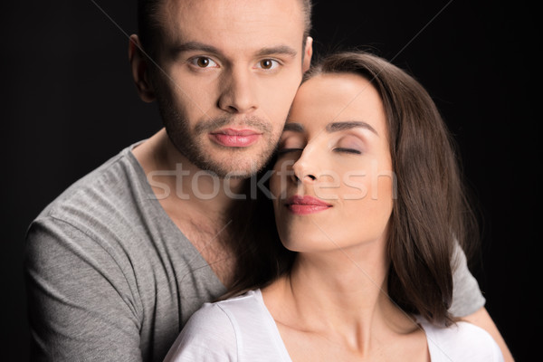 portrait of man looking to camera while hugging woman on black Stock photo © LightFieldStudios