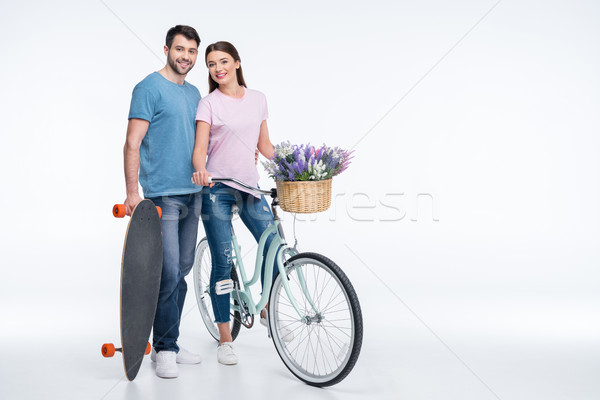 smiling couple with skateboard and bicycle on white Stock photo © LightFieldStudios
