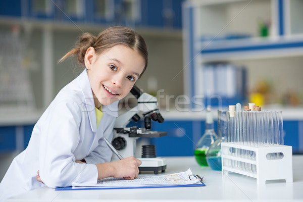 Girl scientist in lab coat writing in clipboard and smiling at camera Stock photo © LightFieldStudios
