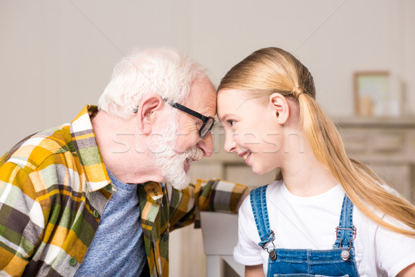 Side view of happy girl and grandfather in eyeglasses touching foreheads and smiling each other Stock photo © LightFieldStudios