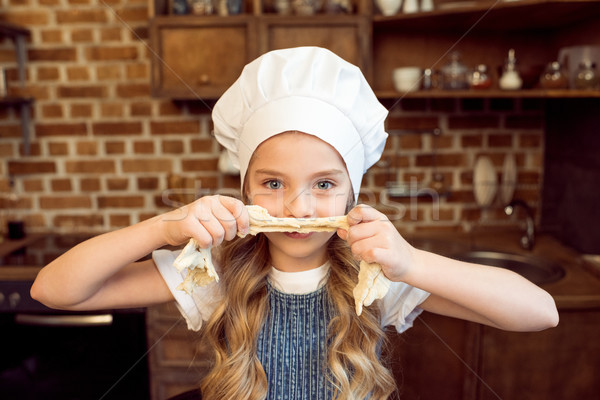 portrait of little girl in chef hat playing with raw dough Stock photo © LightFieldStudios