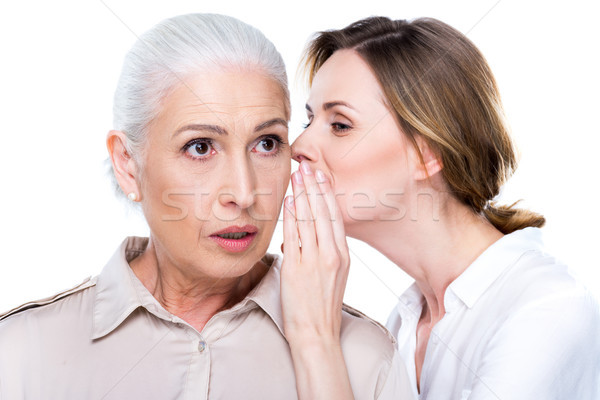adult daughter whispering to senior mother Stock photo © LightFieldStudios
