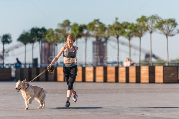 sportswoman jogging with dog Stock photo © LightFieldStudios