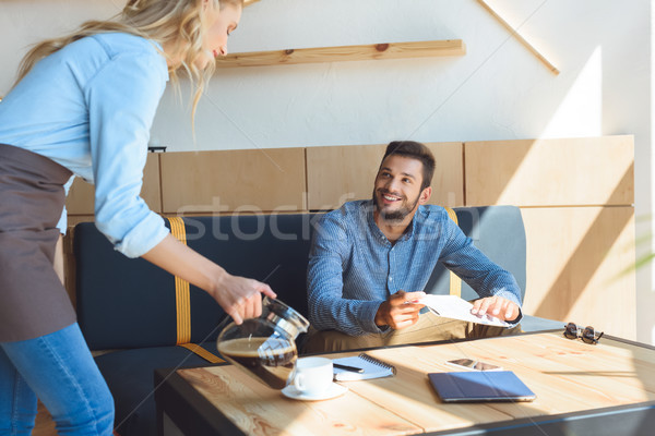 waitress pouring coffee to client Stock photo © LightFieldStudios