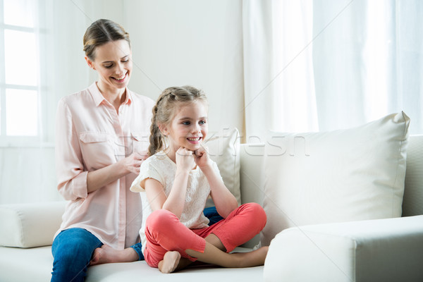 smiling mother pleaching daughter's hair in braids at home Stock photo © LightFieldStudios
