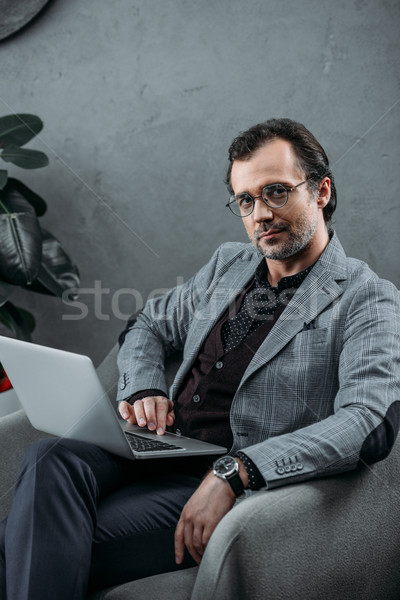 ビジネスマン ラップトップを使用して 眼鏡 見える カメラ ストックフォト © LightFieldStudios