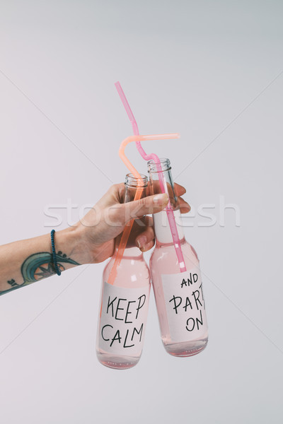 bottles of alcohol beverages in hand Stock photo © LightFieldStudios