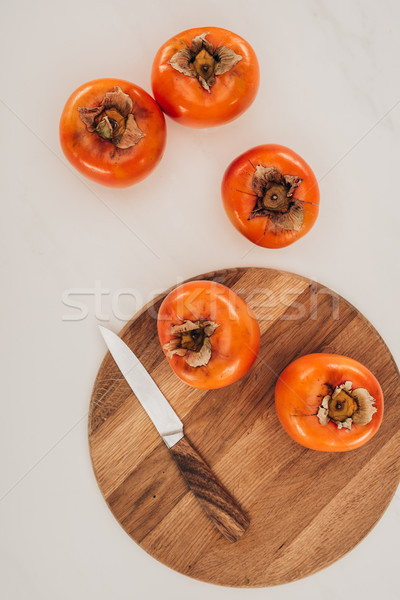 top view of persimmons with knife and wooden board isolated on white Stock photo © LightFieldStudios