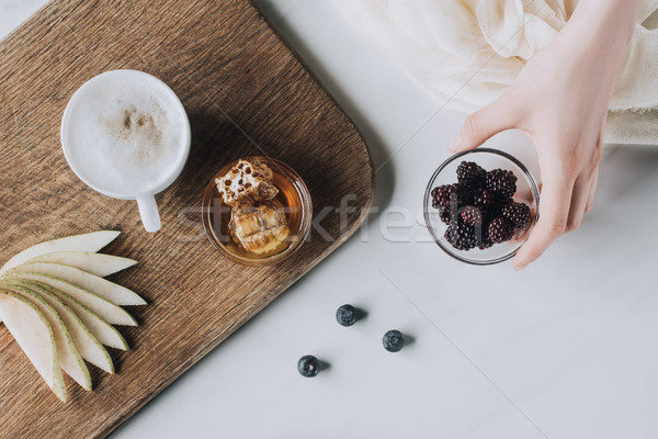 cropped shot of hand holding bowl with blackberries, cup of cappuccino and honey on grey Stock photo © LightFieldStudios