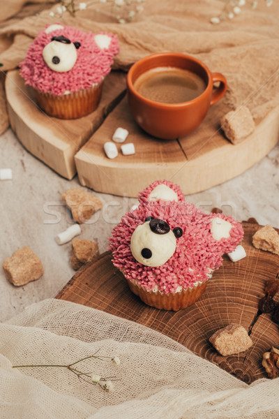 close-up view of delicious sweet cupcakes in shape of bears and cup of coffee on table Stock photo © LightFieldStudios