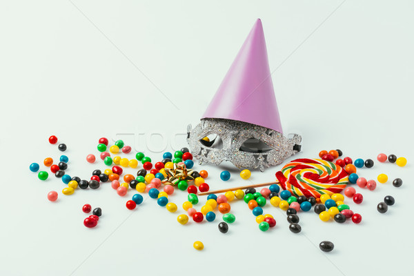 close up view of masquerade mask, party cone and sweets isolated on grey   Stock photo © LightFieldStudios