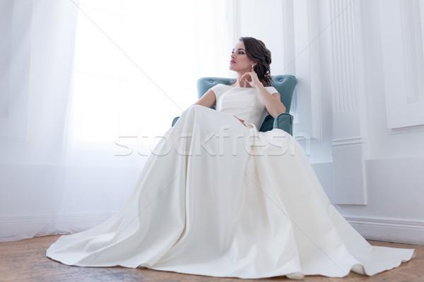 Anziehend Brünette Frau Hochzeitskleid Sitzung Sessel Stock foto © LightFieldStudios