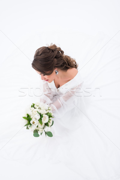 overhead view of elegant bride in traditional dress holding wedding bouquet, isolated on white Stock photo © LightFieldStudios