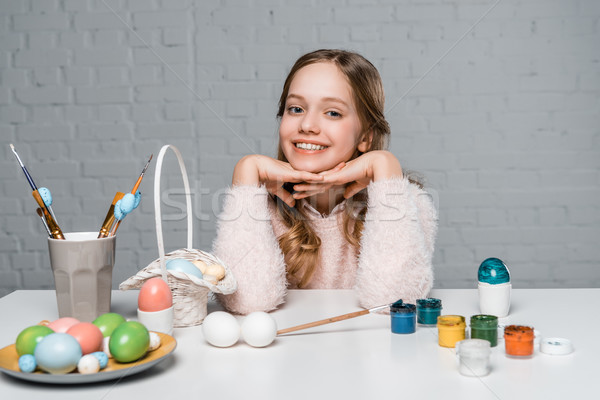 adorable happy girl smiling at camera while sitting at table with paints, basket and easter eggs Stock photo © LightFieldStudios
