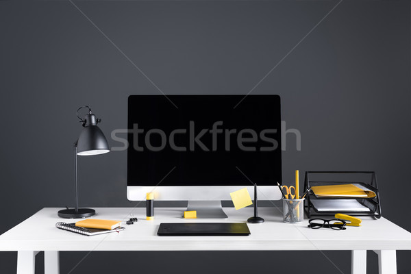desktop computer with blank screen, graphics tablet and office supplies at workplace Stock photo © LightFieldStudios