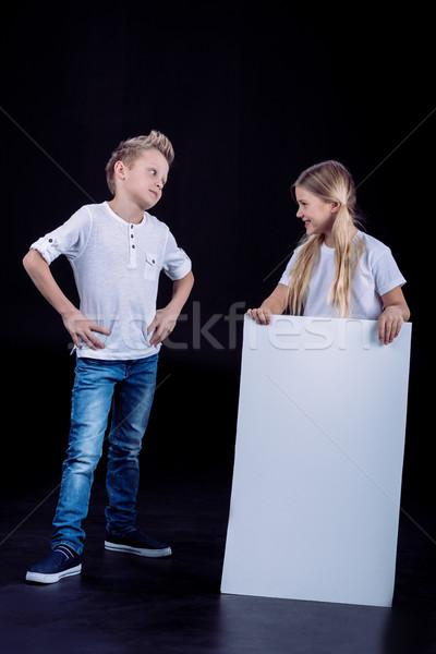 Smiling siblings with blank card Stock photo © LightFieldStudios