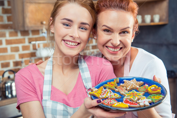 Mother and daughter holding cookies Stock photo © LightFieldStudios