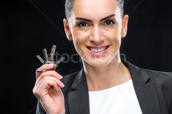 Businesswoman holding keys Stock photo © LightFieldStudios