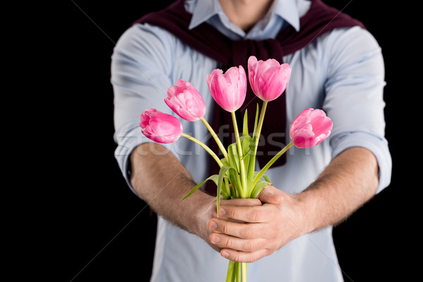 Close-up partial view of man presenting beautiful pink tulips on black, international womens day con Stock photo © LightFieldStudios