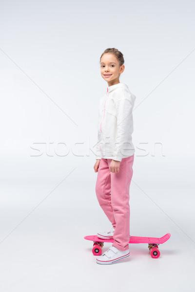 side view of smiling girl standing on skateboard on white Stock photo © LightFieldStudios