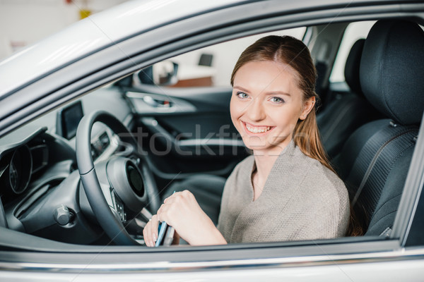 Happy young woman driver sitting in new car with key in hands Stock photo © LightFieldStudios
