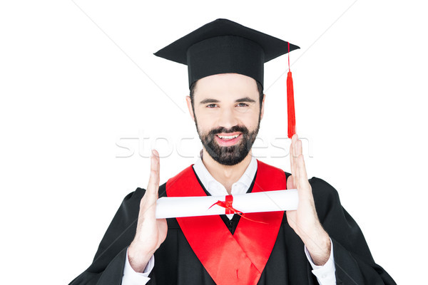 Happy young man in graduation hat holding diploma and looking at camera Stock photo © LightFieldStudios
