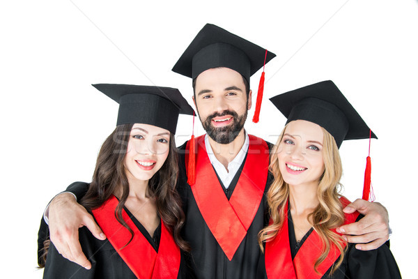 Happy students in academic caps standing embracing and smiling at camera Stock photo © LightFieldStudios