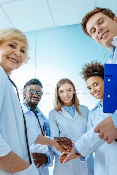 Grupo médicos médicos pie círculo tomados de las manos Foto stock © LightFieldStudios