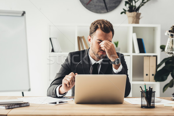 Yorgun işadamı işyeri genç oturma dizüstü bilgisayar Stok fotoğraf © LightFieldStudios