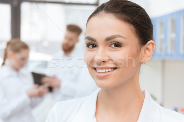 Close-up portrait of young woman in white coat smiling at camera in lab Stock photo © LightFieldStudios