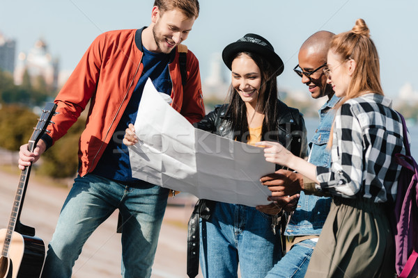 multicultural friends choosing destination on map Stock photo © LightFieldStudios