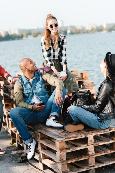 multicultural friends resting on pier Stock photo © LightFieldStudios