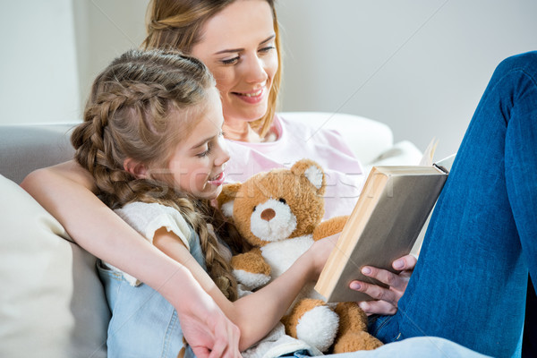 Stock photo: Smiling mother and daughter with teddy bear reading book on sofa